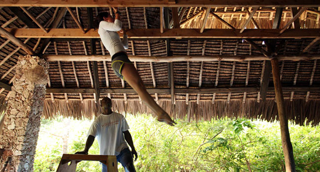 Woman doing pull-ups in a thatched hut