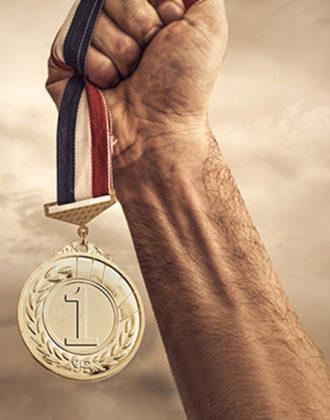 Hand holding a gold medal aloft