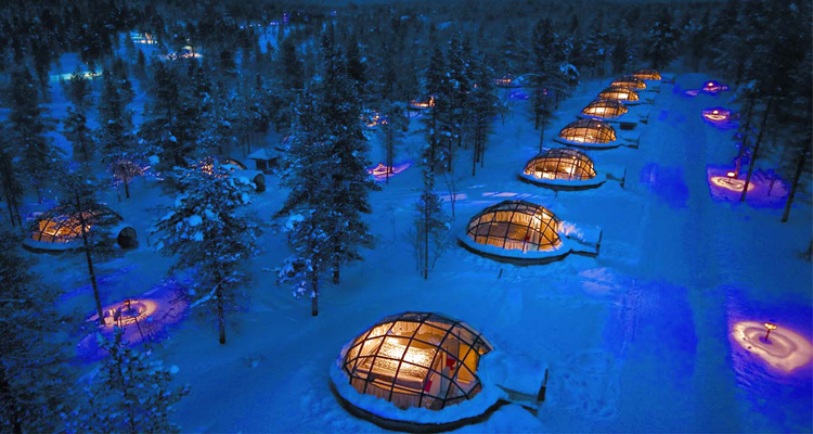 Kakslautannen glass igloos lit up at night in a snowy winter landscape