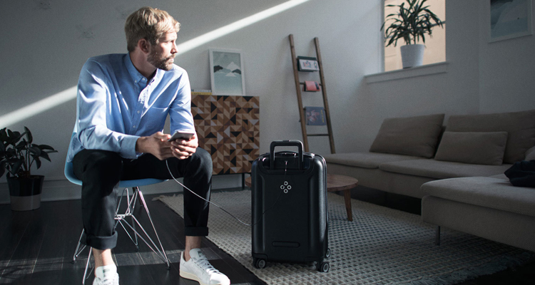 A man charging his phone via his Bluesmart smart luggage case