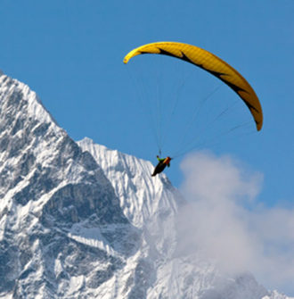 Raise a Glass to the Risk-Takers: Paraglider over snowcapped mountains