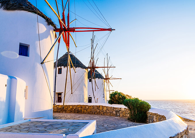 Windmills by the sea at sunset in Mykonos