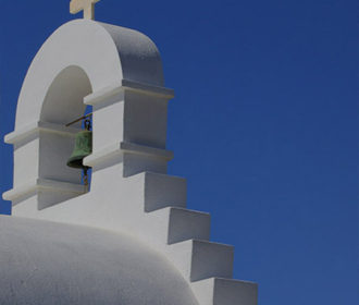 Oykos: Island Escape - White Greek church against a blue sky