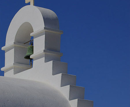 Oykos: Island Escape - White Greek church against a blue sky