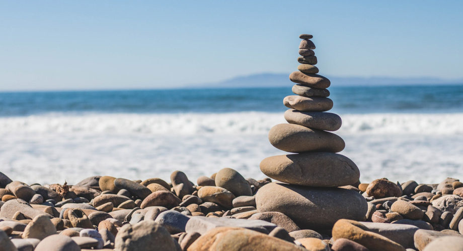 Balancing rocks on a beach- wellness and the key to productivity