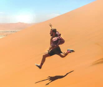 Motivate your staff - man running down a sand dune in the desert