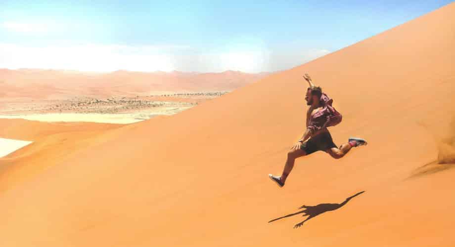 Motivate your staff - a man runs down a sand dune
